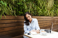 Busy businesswoman working at an outdoor cafe - VABF01395