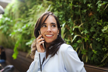 Smiling businesswoman on cell phone in garden cafe - VABF01401