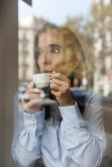 Businesswoman drinking espresso behind window pane - VABF01410