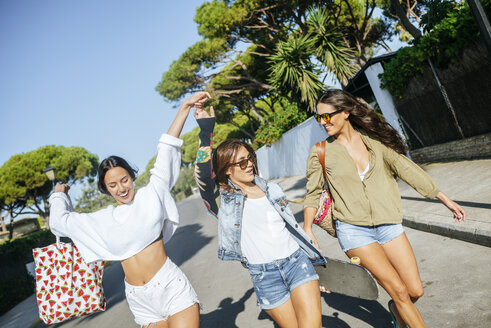 Three happy young women walking on the street - KIJF01736
