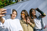 Three smiling young women taking selfie with smartphone - KIJF01742