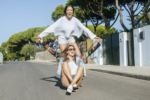 Two laughing friends together on skateboard - KIJF01745