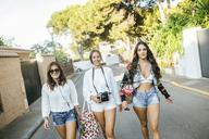 Portrait of three smiling friends walking on residential street - KIJF01760
