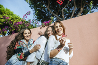 Portrait of three laughing young women with fidget spinner - KIJF01769