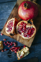 Sliced and whole pomegranate on cutting board - KIJF01772