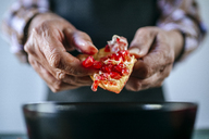 Man's hands peeling a pomegranate, close-up - KIJF01775