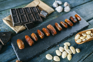 Dates, dark chocolate, almonds and dried figs on wood - KIJF01781