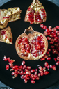 Half of pomegranate and pomegranate seed on black plate, close-up - KIJF01784