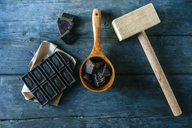 Dark chocolate on paper, wooden spoon and wooden hammer on blue wood - KIJF01790