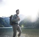Austria, Tyrol, young man hiking at mountain lake - UUF12470
