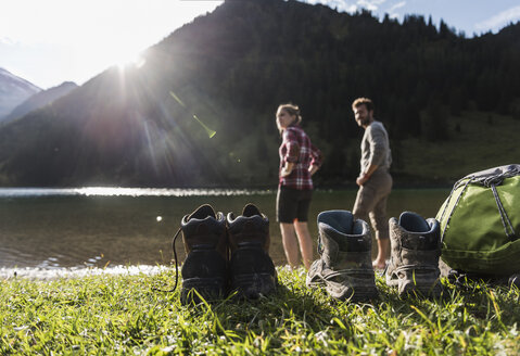 Austria, Tyrol, hiking shoes and couple refreshing in mountain lake - UUF12476