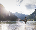 Austria, Tyrol, hiker splashing in mountain lake - UUF12479