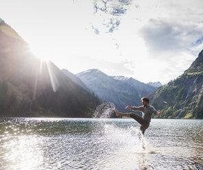 Austria, Tyrol, hiker splashing in mountain lake - UUF12479