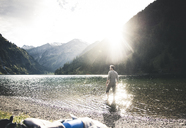 Austria, Tyrol, hiker refreshing in mountain lake - UUF12482