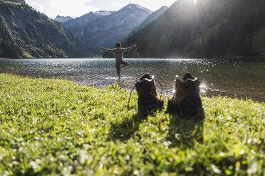 Austria, Tyrol, hiking shoes and man in yoga pose in mountain lake - UUF12485