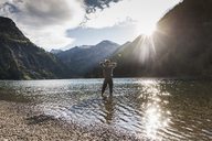 Austria, Tyrol, hiker refreshing in mountain lake - UUF12491