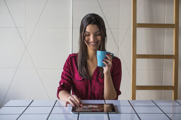 Woman looking at tablet computer and smiling - MOMF00335