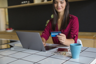 Young woman using laptop, paying with credit card - MOMF00338