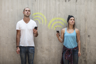 Man and woman holding their phones with wifi sign in chalk - ZEF14873