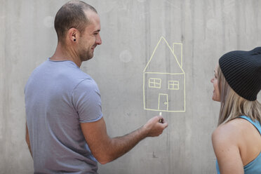 Man and woman drawing a house with chalk on concrete wall - ZEF14876