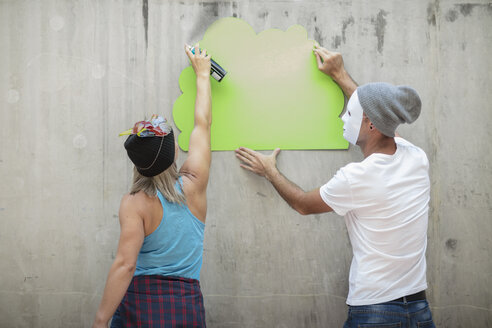 Man and woman wearing masks spray painting a concrete wall - ZEF14879