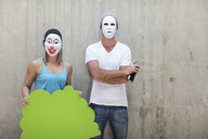 Man and woman wearing masks standing next to a concrete wall - ZEF14882