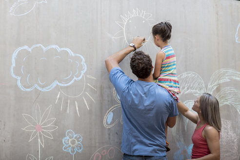 Family drawing colourful pictures with chalk on a concrete wall - ZEF14885