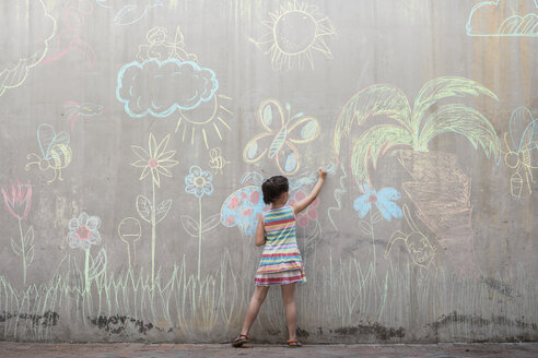 Girl drawing colourful pictures with chalk on a concrete wall - ZEF14888