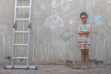 Girl standing next to colourful pictures on a concrete wall - ZEF14891