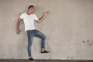 Man pretending to be dead standing with chalk outline drawn on concrete wall - ZEF14894