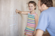 Father and daughter playing tic tac toe with chalk on a concrete wall - ZEF14897