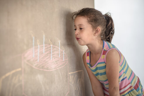 Girl pretending to blow out chalk birthday cake and candle drawing on concrete wall - ZEF14900