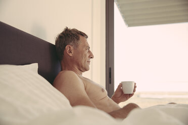 Relaxed man in bed holding cup of coffee - MFF04248