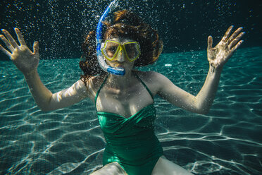 Portrait of woman with diving goggles and snorkel underwater in a swimming pool - MFF04251