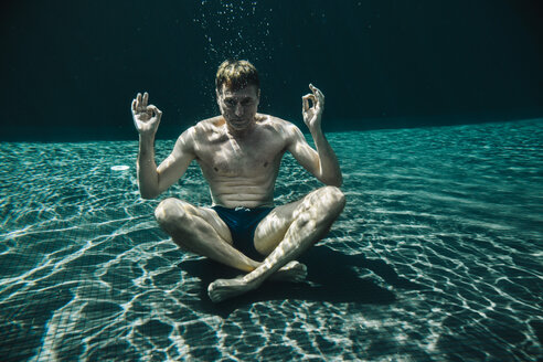 Man sitting in yoga pose underwater in a swimming pool - MFF04254