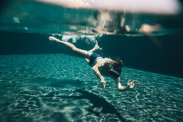Man diving in a swimming pool wearing VR glasses - MFF04257