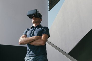 Mature man wearing VR glasses standing between walls of modern architecture - MFF04260