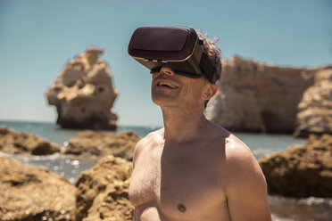 Mature man wearing VR glasses between rocks on beach - MFF04263