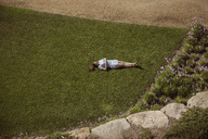 Woman lying on lawn in garden - MFF04266