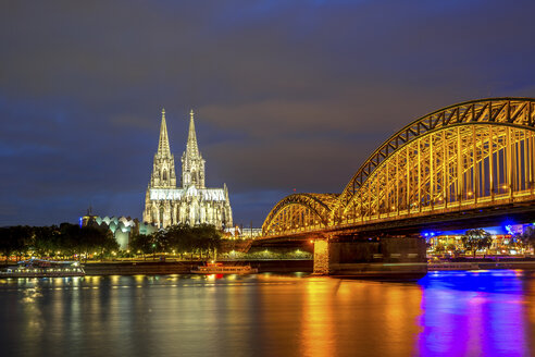 Germany, Cologne, illuminated Cologne Cathedral and Hohenzollern bridge at night - PUF00973