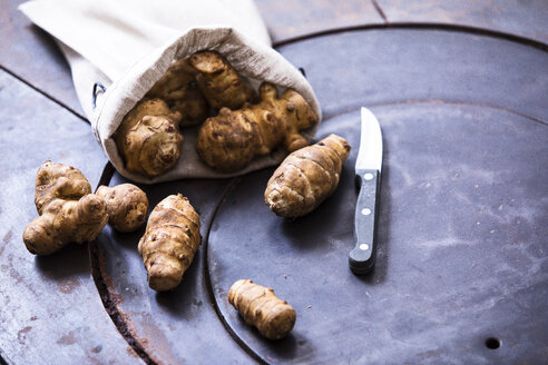 Jerusalem artichokes, sachet and kitchen knife on metal - MAEF12465