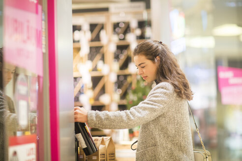 Young woman choosing bottle of red wine in supermarket - SGF02125