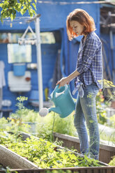 Young woman watering plants in garden - VPIF00271