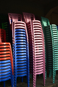 Stacks of coloured plastic chairs - IGGF00249