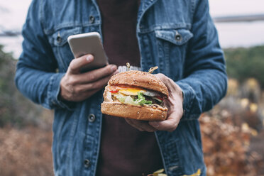 Man with burger and smartphone - VPIF00295