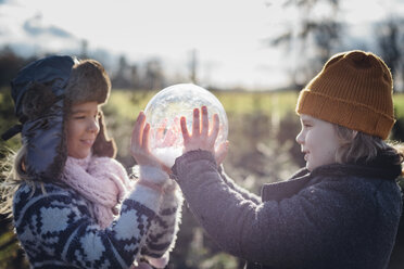 Brother and sister looking into crystal ball filled with snow, making a wish - MJF02212