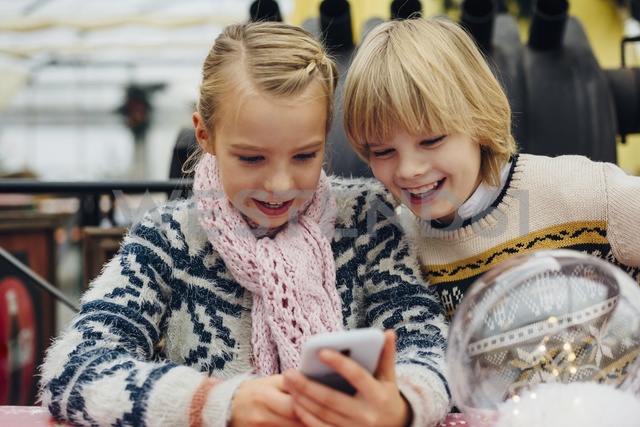Brother and sister sending text messages with Christmas wishes on smartphone - MJF02227