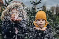 Brother and sister having fun with snow before Christmas - MJF02233