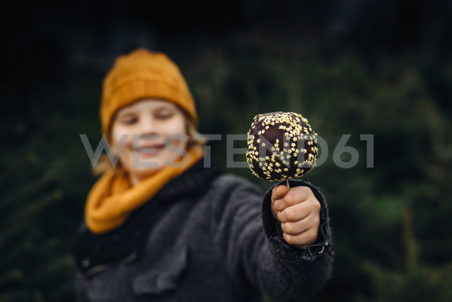 Little boy standing in front of fir trees holding chocolate dipped apple - MJF02242