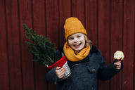 Laughing boy standing in front of wooden wall with potted Chritsmas tree and candied apple - MJF02251